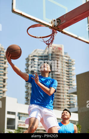young asian adult players playing basketball on outdoor court. - Stock Photo