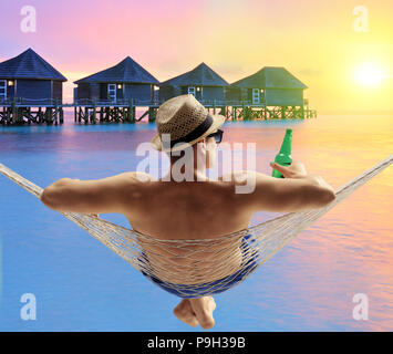 Young man with a bottle of beer lying in a hammock at a water cottages resort on a Maldives island - Stock Photo