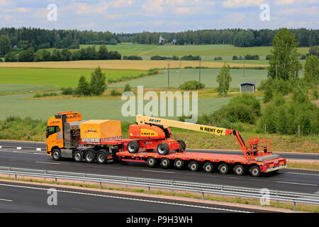 Yellow Volvo FH semi trailer of Rantala transports JLG 860SJ Telescopic Boom Lift on trailer along motorway in summer. Salo, Finland - July 13, 2018. - Stock Photo