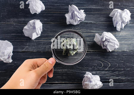 Crumpled dollar among white paper balls on a dark background. The concept of a good idea, brainstorming, a successful solution and a search of differe - Stock Photo