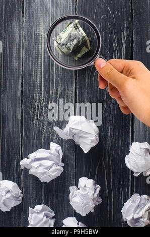 Crumpled dollar on top of white paper balls on a dark background. The best idea, the process of thinking about new business solutions, the investment  - Stock Photo