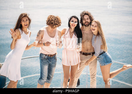 Young wealthy friends, dressed in summer clothing for boat trip having fun, drinking wine, on a bow of luxury yacht. - Stock Photo