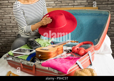 Woman hand packing a luggage for a new journey and travel for a long weekend - Stock Photo