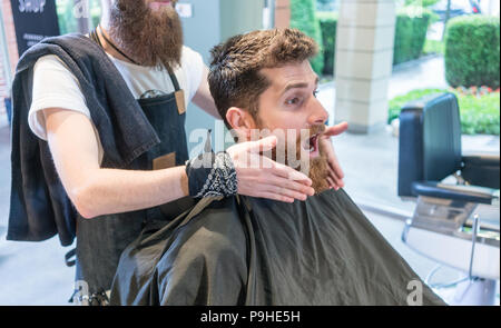 Redhead bearded young man making a funny face before a change of look - Stock Photo