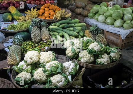 Farmers' food market stall with variety of organic vegetable. Vendor serving and chating with customers. Fruits and vegetables at the vegetable street - Stock Photo