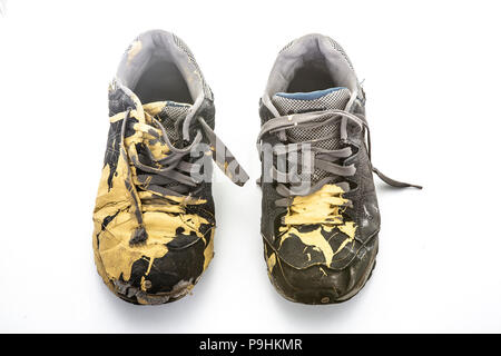 Pair of old paint covered training shoes on a white background - Stock Photo