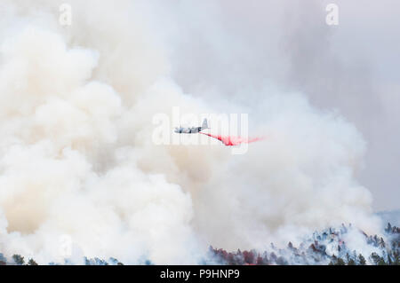An Air Force C-130 Hercules aircraft, equipped with a Modular Airborne Firefighting System, drops slurry to support fire suppression efforts July 4, 2018. The mission is provided by the Department of Defense at the request of the U.S. Forest Service, which owns the MAFFS equipment and provides the slurry.    (U.S. Army National Guard photo by Sgt. 1st Class Marc Belo) - Stock Photo