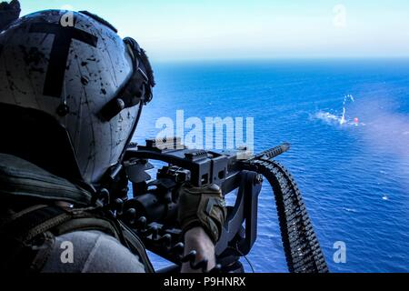 """180716-N-NO146-1001 U.S. 5TH FLEET AREA OF OPERATIONS (July 16, 2018) Naval Aircrewman (Helicopter) 3rd Class Parker Thompson fires a .50-caliber machine gun at a """"killer tomato"""" inflatable target from an MH-60R Seahawk helicopter assigned to the """"Vipers"""" of Helicopter Maritime Strike Squadron (HSM) 48, attached to the guided-missile destroyer USS Jason Dunham (DDG 109). Dunham is deployed to the U.S. 5th Fleet area of operations in support of naval operations to ensure maritime stability and security in the Central region, connecting the Mediterranean and the Pacific through the western India - Stock Photo"""
