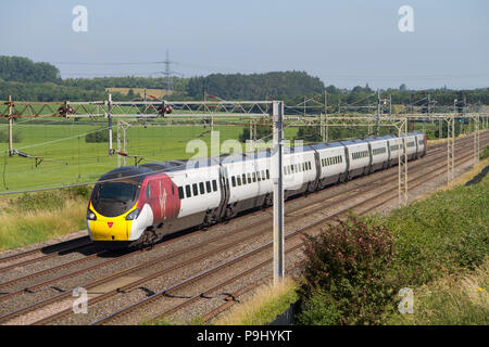 A class 390 Pendolino number 390016 in a revised Virgin livery working a Virgin Trains West Coast service at Ledburn Junction on the 30th June 2018. - Stock Photo