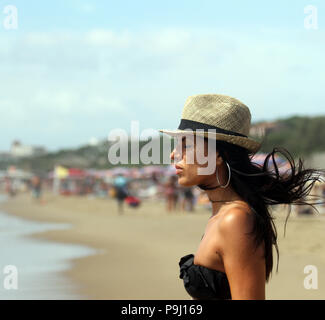 Beautiful young woman meditates on the beach with her eyes closed and her hair in the wind. The sea on the background. Sabaudia, Lazio, Italy - Stock Photo