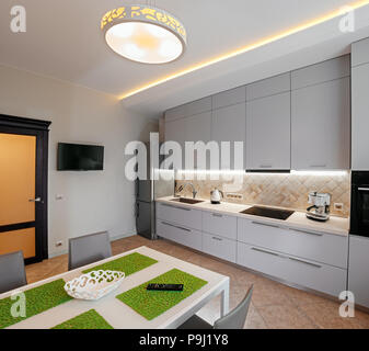 Light and modern kitchen interior with white dining table, brown tile floor, refrigerator and appliances - Stock Photo
