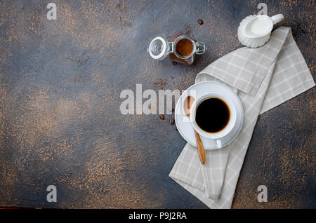 black strong coffee in a white cup with saucer, milkman and a bank of coffee powder on a dark concrete old background - Stock Photo