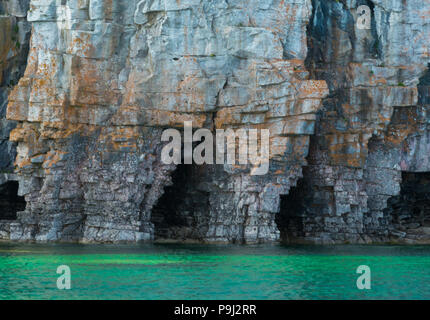 Bright clear aqua green water on Bruce Peninsula with big limestone caves in the cliff at CyprusLake National Park - Stock Photo