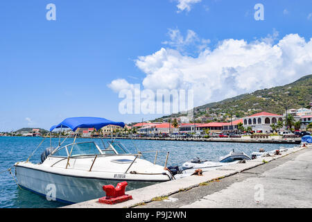 Saint Thomas, US Virgin Islands - April 01 2014: A sailboat and some speedboats docked in downtown Saint Thomas in the US Virgin Islands. - Stock Photo