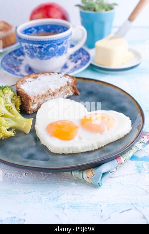 Fried eggs in the form of heart. On a dark plate with broccoli and toast. Blue cup with tea, butter for breakfast and cupcakes. On a light colored background. Free space for text or advertising - Stock Photo