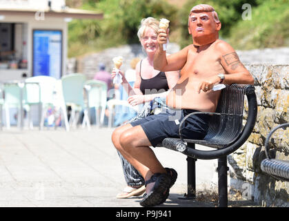 Man in Donald Trump mask enjoying the sun in Plymouth,Devon,UK - Stock Photo