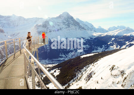 People taking panoramic mountain photos on the Grindelwald First Cliff Walk platform - Stock Photo