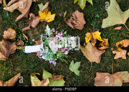 Bouquet of orchids and roses lying on grass near maple leaves - Stock Photo