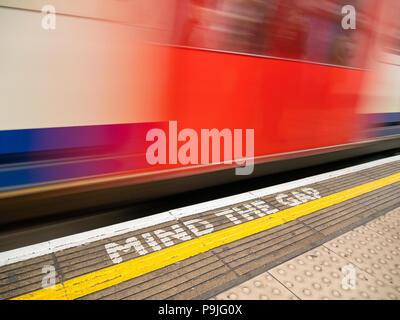 Blur of London Underground train and Mind The Gap warning sign on platform edge, London, UK - Stock Photo