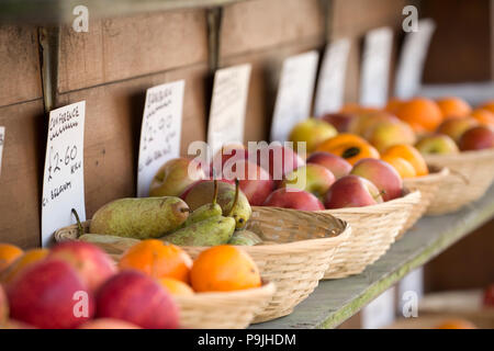 Bowls of fruit for sale including oranges, pears and apples on display outside a greengrocers shop in North Dorset England UK GB. - Stock Photo