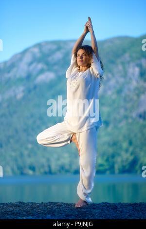 Young woman practicing yoga outdoors in the nature at a lake,Vriksasana or Vrksasana, standing tree pose - Stock Photo