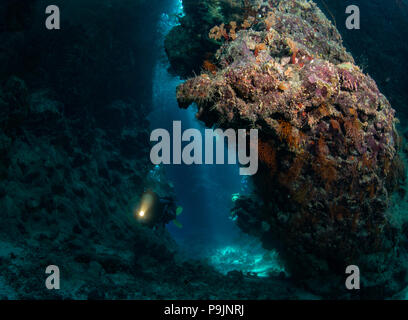 Woman diver explores St John's Caves in the Red Sea, Egypt - Stock Photo