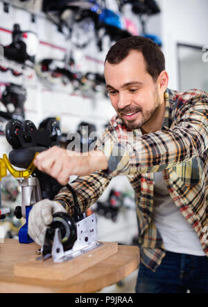 Young satisfied pleasant  male repairer fixing roller-skates in sports store - Stock Photo