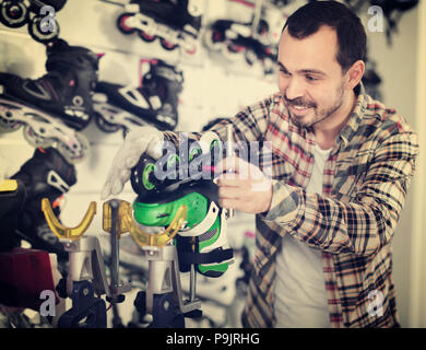 Young pleasant male repairer fixing roller-skates in sports store - Stock Photo