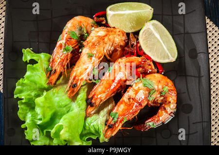 Shrimps roasted with onion, garlic and chili served on black plate. - Stock Photo