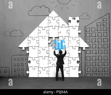 Putting last blue puzzles in house shape on concrete wall - Stock Photo