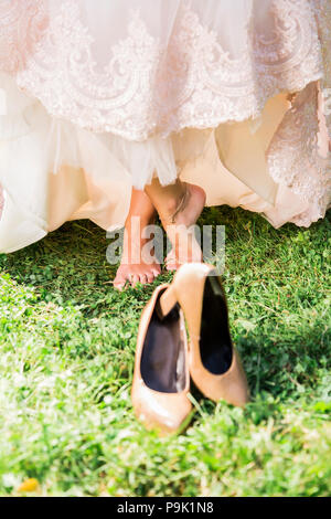 Barefoot bride on grass with shoes - Stock Photo