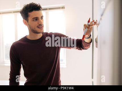 Businessman writing on whiteboard in office and explaining. Entrepreneur using whiteboard to discuss business plans and ideas. - Stock Photo
