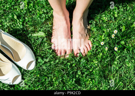Barefoot bride on grass in summer time - Stock Photo