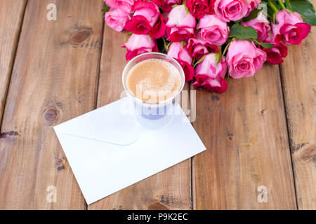 A bouquet of fresh pink roses and a glass of espresso. Wooden background. Free space for text or postcards. White envelope for writing. - Stock Photo