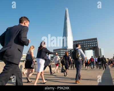 Commuters crossing London Bridge with the Shard in the background, London, UK - Stock Photo