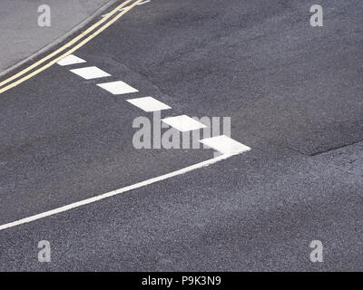 looking down from above to the give way road markings from above and to one side. New painted lines on good road surface - Stock Photo