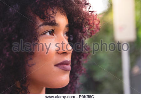 Close up profile beautiful young student tourist girl looking to the side. Concept of hope, plans, future, goal. She is black, on her early twenties,  - Stock Photo