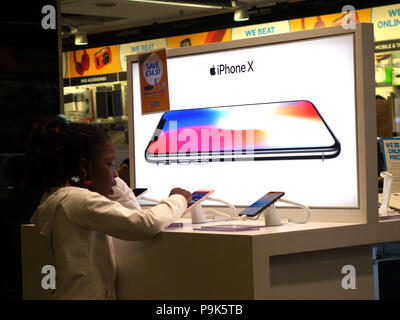 Young people looking at the electronic items on sale in the Duty Free Lounge Electronic section at Manchester Airport. IPhone X Advert - Stock Photo