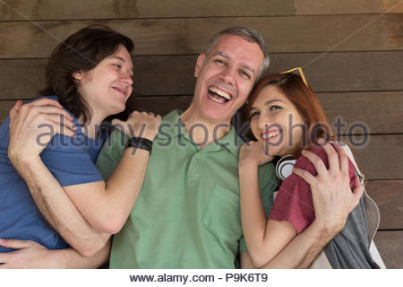 Portrait of Mature dad and teenage son and daughter holding each other. Father Day. Concept of bonding, enjoyment, fatherhood, affection. - Stock Photo