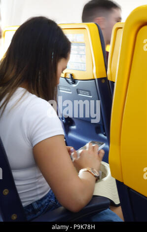 A woman takes her seat and sends a mobile text while she sits in the plane cabin on a Ryanair flight - Stock Photo