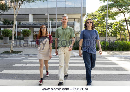 Mature dad with children are walking down the street, crossing the crosswalk. Concept of family, relationship, togetherness. - Stock Photo