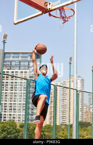 young asian male player playing basketball on outdoor court. - Stock Photo