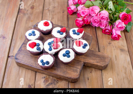 Chocolate muffins with raspberries and blueberries, and white cheese cream, on a brown wooden board. A bouquet of fresh pink roses for lovers. Homemade pastries for breakfast. Free space for text. - Stock Photo
