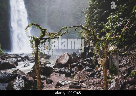 Tropical wedding ceremony with waterfall view in jungle canyon. Decorated with green ivy, old branches and hanging lamps - Stock Photo