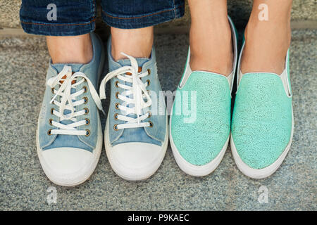 two pairs of girl's feet in sneakers - Stock Photo