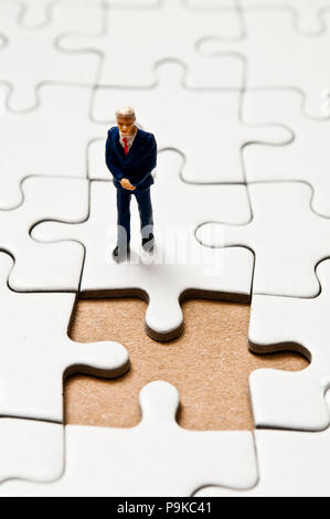 businessman miniature figurine standing on a jigsaw puzzle with a missing piece, business solutions concept - Stock Photo