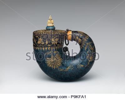 Powder Flask, 17th century, Indian, possibly Deccan, Horn, lacquer, ivory, bone, gold, silver, copper alloy, iron, pigment, L. 7 3/4 in. (19.7 cm); W. 7 7/8 in. (20 cm); Wt. 1 lb. 4 oz. (576 g), Firearms Accessories-Flasks & Primers, Designed to hold gunpowder, this flask, shaped like a nautilus shell, is made of wood, covered with a marbled pattern of blue and black lacquer, and bordered by delicate floral designs in gold. The skill and sophistication of the decoration place this work among the most beautiful objects of its kind from Mughal India. - Stock Photo