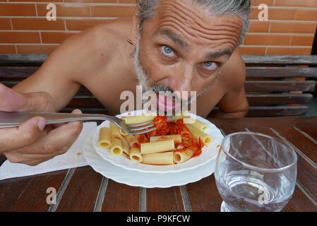 shirtless mature man eating maccheroni Italian pasta dish - Stock Photo