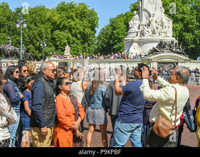 Tourists taking pictures of other people in their tour party outside Buckingham Place - Stock Photo