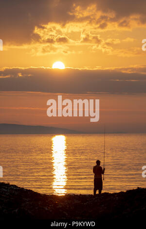 Penmon Point, Anglesey, Wales, 18th July 2018. UK Weather: At the end of a hot day on Anglesey and clearing skies over the Island the day ends with a stunning sunset. A fisherman waiting to cast into the sea against a backdrop of a beautiful sunset at Penmon Point, Anglesey – Credit: DGDImages/Alamy Live News - Stock Photo